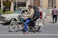 Coppia sposata con la guida della figlia sul motociclo attraverso la città s Immagine Stock Libera da Diritti
