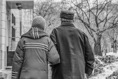 Coppia sposata dei pensionati che camminano a braccetto nella via con le case e gli alberi e nella neve sporca nell'inverno ed in fotografia stock
