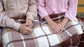 Coppia sposata matura che riposa sul banco di parco coperto di coperta, casa di cura fotografia stock libera da diritti