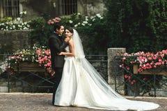 Coppia sposata romantica felice che abbraccia sul ponte di pietra con flowe Immagine Stock Libera da Diritti