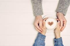 Coppia tenersi per mano con il caffè sulla tavola bianca, vista superiore Fotografia Stock Libera da Diritti