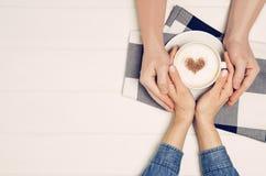 Coppia tenersi per mano con il caffè sulla tavola bianca, vista superiore Fotografia Stock