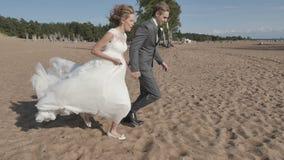 Coppia tenersi per mano correre sulla spiaggia, il movimento della macchina fotografica dal lato stock footage