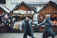 Coppia tenersi per mano la camminata sul mercato di natale della città che guarda le FO fotografie stock libere da diritti