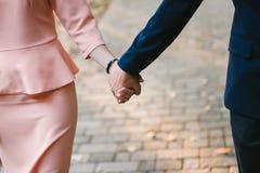 coppia tenersi per mano strettamente, passeggiata sul percorso cobbled Fotografia Stock