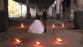 Coppie in abiti nuziali con trucco di Halloween con fuoco che brucia intorno loro stock footage