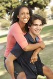 Coppie adolescenti che hanno divertimento in campo da giuoco fotografia stock libera da diritti