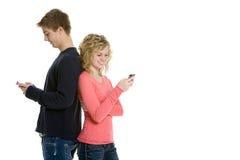 Coppie adolescenti che si levano in piedi per mezzo dei telefoni delle cellule Immagine Stock