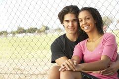Coppie adolescenti che si siedono nel campo da giuoco Fotografia Stock