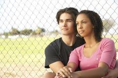 Coppie adolescenti che si siedono nel campo da giuoco fotografia stock libera da diritti