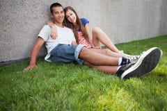 Coppie adolescenti che si siedono sull'erba Fotografia Stock