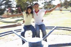 Coppie adolescenti divertendosi sulla rotonda fotografia stock