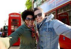 Coppie adolescenti felici che prendono selfie nella città di Londra Immagini Stock