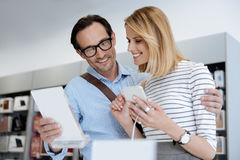 Coppie adorabili che cercano nuovo smartphone al deposito Fotografie Stock