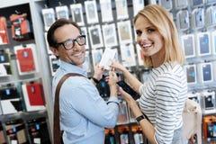 Coppie adorabili che posano con la cassa e sorridere del telefono Immagini Stock Libere da Diritti