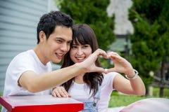 Coppie adorabili con il segno della mano di amore Fotografia Stock Libera da Diritti