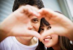 Coppie adorabili con il segno della mano di amore Immagini Stock