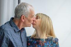 Coppie adorabili con la differenza di età che bacia vicino alla finestra aperta dentro la Camera durante il tempo di primavera immagine stock libera da diritti