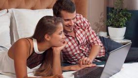 Coppie adorabili facendo uso del computer portatile alla loro camera di albergo, mentre mangiando caffè immagini stock libere da diritti