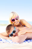 Coppie adulte che prendono il sole alla spiaggia Fotografia Stock Libera da Diritti