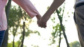Coppie adulte che si tengono per mano camminata nel parco, insieme con le difficoltà di vita fotografia stock libera da diritti