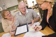 Coppie adulte senior che superano le carte nella loro casa con l'agente Immagine Stock