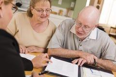Coppie adulte senior che superano le carte nella loro casa con l'agente Fotografia Stock Libera da Diritti