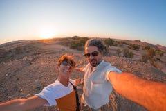 Coppie adulte sorridenti che prendono selfie nel deserto di Namib, parco nazionale di Namib Naukluft, destinazione principale di  fotografia stock