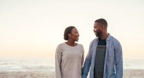 Coppie africane sorridenti che camminano insieme giù una spiaggia al crepuscolo Fotografie Stock