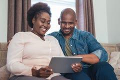 Coppie africane sorridenti che si siedono a casa facendo uso di una compressa digitale Immagini Stock