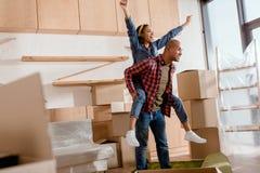 coppie afroamericane emozionanti che trasportano sulle spalle in nuovo appartamento fotografia stock