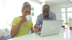 Coppie afroamericane mature facendo uso del computer portatile a casa stock footage