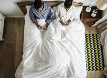 Coppie afroamericane sul letto facendo uso dei cellulari Fotografia Stock