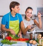 Coppie alla cucina con le verdure alla tavola Fotografia Stock