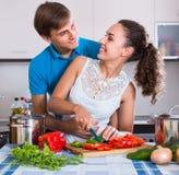Coppie alla cucina con le verdure alla tavola Fotografie Stock Libere da Diritti