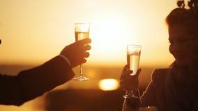 Coppie alla data romantica al ristorante della spiaggia al tramonto video d archivio