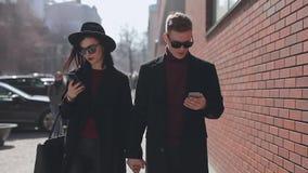 Coppie alla moda che guardano giù nei loro smartphones che camminano lungo la via della città video d archivio
