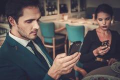 Coppie alla moda con i telefoni cellulari in un ristorante fotografia stock libera da diritti