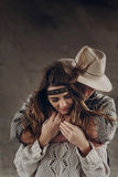 Coppie alla moda dei pantaloni a vita bassa che abbracciano delicatamente uomo in touchi sensuale del cappello fotografie stock