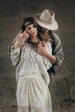 Coppie alla moda dei pantaloni a vita bassa che abbracciano delicatamente uomo in touchi sensuale del cappello immagini stock libere da diritti
