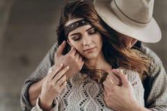 Coppie alla moda dei pantaloni a vita bassa che abbracciano delicatamente uomo in touchi sensuale del cappello fotografia stock libera da diritti