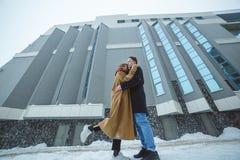 Coppie alla moda dei pantaloni a vita bassa che abbracciano vicino alla costruzione moderna nell'orario invernale Immagini Stock
