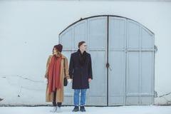 Coppie alla moda in serie classica che sta vicino alla costruzione storica bianca Abbigliamento alla moda di inverno Immagine Stock Libera da Diritti