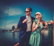 Coppie alla moda su un yacht di lusso Immagine Stock Libera da Diritti