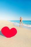 Coppie alla spiaggia del mare ed al grande cuore rosso Fotografie Stock Libere da Diritti