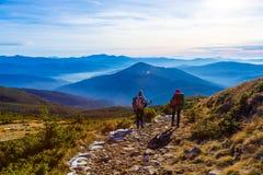 Coppie allegre che camminano sul tramonto nebbioso delle montagne della strada rurale Fotografia Stock Libera da Diritti