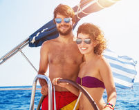 Coppie allegre che conducono barca a vela Immagini Stock Libere da Diritti
