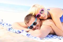 Coppie allegre che prendono il sole alla spiaggia Fotografia Stock