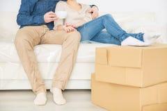 Coppie allegre che riposano sul sofà fotografia stock libera da diritti