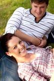 Coppie allegre degli allievi che si siedono sull'erba Fotografie Stock Libere da Diritti
